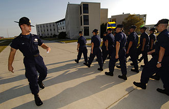 U.S. military instructor badges - A Coast Guard Company Commander marches his trainees, wearing the Company Commander Insignia over his service tape of his ODU
