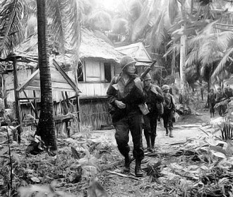 Dinagat Islands - Soldiers of the 6th Ranger Battalion move through a village on Dinagat Island, 18 October 1944.