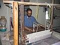 A man weaving in a chamber in lower courtyard.jpg