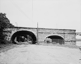 Aqueduct Bridge (Potomac River) - Side view of second Aqueduct Bridge abutment, with Water Street and Whitehurst Freeway visible through the arch.