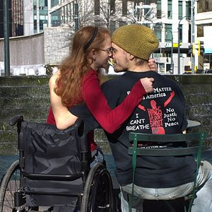 A woman in a wheelchair embracing a man in a chair