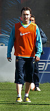 A man wearing long, dark blue shorts and a light blue sweatshirt under an orange bib.