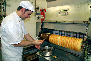 Baumkuchen - Baking demonstration in Germany, here: application of the couverture chocolate.
