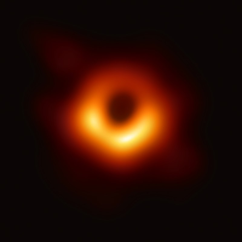 Blackness of space with black marked as center of donut of orange and red gases