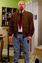 Un homme chauve, avec du faux sang sur le visage et sur son tee-shirt, vêtu comme le personnage de Butch Coolidge dans le film.