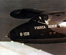 "A close-up of a jet in flight, the pilot is wearing a white helmet. On the nose of the plane are the Spanish words ""Fuerza Aerea Argentina"" and the designation code ""B-108""."