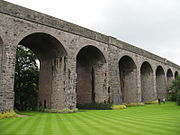 A series of seven stone archways, connected to stone parapet above grass area.