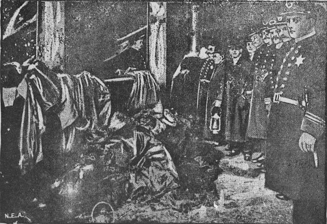 Black and white photo depicting the police standing over a pile of bodies