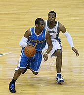 "A black basketball player, wearing a blue jersey with a word ""New Orleans"" and the number ""3"" written in the front, dribbles the ball in front of another player"