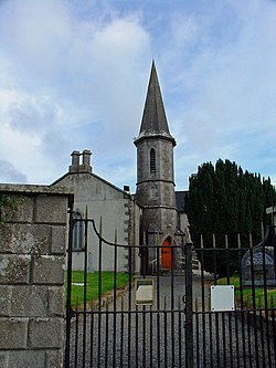 Behind a wrought iron gate sits a church with grey stone quoins. An octagonal steeple with a tall pointed roof adjoins the right side of the nave and contains a ground-level entry with red door.