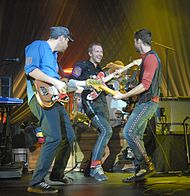 A photo of Coldplay, with three members playing various guitars.