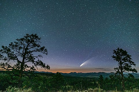 Comet NEOWISE framed in a starry sky behind the cinder cones near the San Francisco Peaks near Flagstaff, Arizona