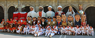 San Fermín - Pamplona's Giants and Big-heads parade family photo. From back to front and left to right we can see the American, Asian, African and European pairs of giants (last row), the six kilikis and the 5 big-heads (second row), the zaldikos, and members of the parade who carry the figures (front row).