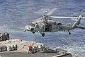 Crew member attaches cargo to a Sea Hawk at sea. (8692079213).jpg