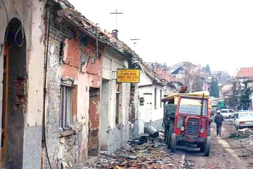 A street of ruined buildings with rubble strewn across the road. A red tractor and other vehicles are visible parked in the background