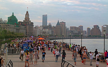 A wide curving walkway along a body of water to the right, crowded with many people and some large orange umbrellas underneath a sky colored by sunset. To the left of the walkway are light brownish-grey stone buildings in various late-19th and early-20th-century architectural styles, with taller buildings in the distance.