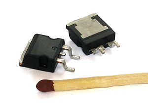 MOSFET - Two power MOSFETs in D2PAK surface-mount packages. Operating as switches, each of these components can sustain a blocking voltage of 120 volts in the OFF state, and can conduct a continuous current of 30 amperes in the ON state, dissipating up to about 100 watts and controlling a load of over 2000 watts. A matchstick is pictured for scale