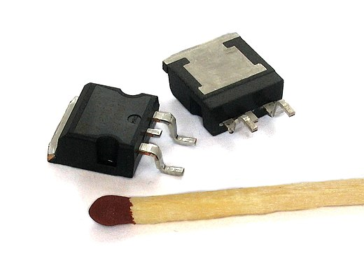 Two power MOSFETs in D2PAK surface-mount packages. Operating as switches, each of these components can sustain a blocking voltage of 120 V in the off state, and can conduct a continuous current of 30 A in the on state, dissipating up to about 100 W and controlling a load of over 2000 W. A matchstick is pictured for scale. D2PAK.JPG