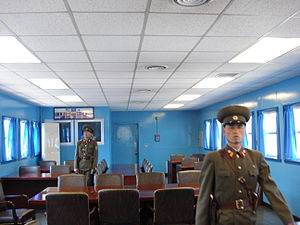 Joint Security Area - Two KPA soldiers standing guard inside a JSA conference room, in front of the door leading to the South Korean side of the JSA. View from north to south.