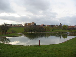 Dackenheim - First hole with water hazard and a view of Dackenheim