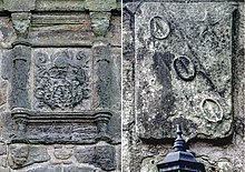 Two stone coats of arms, heavily worn from the weather.