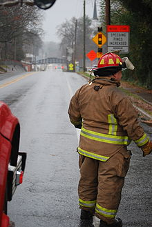 A volunteer firefighter stands to the edge of a road