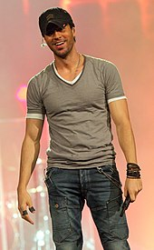 Enrique Iglesias, facing front, holding a microphone.