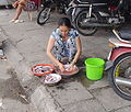 Female cleaning fish squatting.jpg