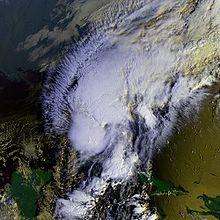 Immagine satellitare di un uragano minimo che attraversa lo stretto della Florida.  Due grandi aree di copertura nuvolosa profonda costituiscono la maggior parte della tempesta, con cirri che si estendono a nord-ovest e una scarsa copertura nuvolosa a nord-est.  La penisola dello Yucatán è visibile in basso a sinistra, parte di Cuba e Haiti sono anche in basso a destra.