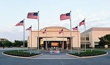 """Acima da porta de uma grande estrutura retangular, relativamente simples, com uma pequena cúpula são as palavras """"George Bush Biblioteca"""".  Em frente do edifício é um pátio circular com uma fonte de água;  oito bandeiras americanas estão posicionados uniformemente ao redor do círculo."""