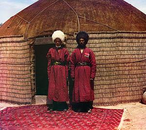 Turkmen rug - Two Turkmen men standing on a carpet in front of a yurt. (1905-1915)