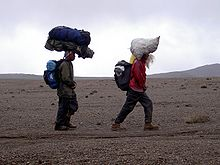 220px-Helpers_carrying_loads_on_their_he