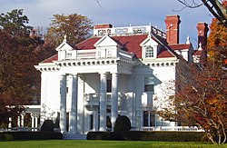 A white house with a colonnaded front and dormer windows in its red roof with brick chimneys on top seen from slightly to the right of center. The sun lights the house from the left and on either side are trees showing fall color