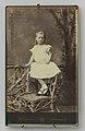 Ingelijst portret Wilhelmina als meisje in wit kanten jurk op rustieke stoel bij hek, in standaard, RP-F-F17411.jpg