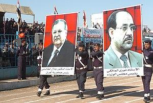 Nouri al-Maliki - Iraqi police officers carry posters of Iraq's President Jalal Talabani and Prime Minister al-Maliki in Najaf, 20 December 2006