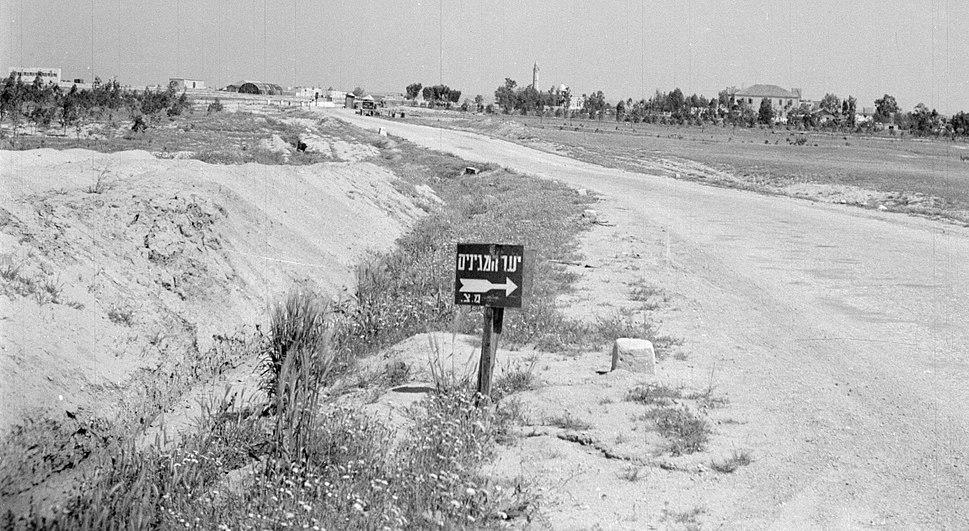 Israël 1948-1949; Negevwoestijn, controlepost. Weg leidend naar een controlepost in de Negevwoestijn, met op de achtergrond een dorp, vermoedelijk Beersjewa (255-0758).A