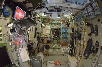 Zvezda (ISS module) - Zvezda aft.  Items in the image include a crucifix, telephoto camera lens, camera flash, zoom camera lens, camera lens, laptop computer, music playback software, a picture of Konstantin Tsiolkovsky, external speakers for a laptop computer, a picture of Yuri Gagarin, a Russian flag, a spaceplane model, a picture of Saint Petersburg, a fluorescent light fitting, several crew patches, and an oscillimeter (combined oscilloscope and multimeter).