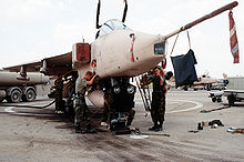 View of mechanics servicing a desert pink jet aircraft.