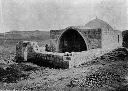 A black-and-white photograph showing a low stone wall enclosing a courtyard in front of a low building with an entry through a pointed arch with a small dome behind