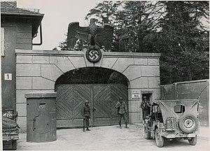 Yolande Beekman - US troops guarding main entrance to Dachau after liberation, 1945.