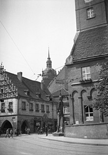 Black and white photograph of Kurfürstenhaus to the left and the New Town Hall to the right, at Hauptstrasse street in Brandenburg an der Havel. In the background is the tower of St. Katharinen church. A statue of knight Roland at the corner of the Town Hall.