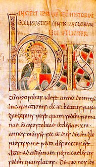 Illuminated manuscript with a forward-facing man in the middle of the large H. Man is carrying a crozier and his head is surrounded by a halo.