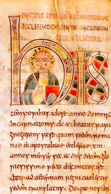 Illuminated manuscript with a forward facing man in the middle of the large H. Man is carrying a crozier and his head is surrounded by a halo.