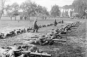 Men of 28th Battalion of the 2nd Australian Division lying prone on the ground to practice Lewis gun drill at Renescure.