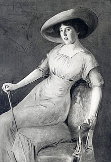 Painting of a dark-haired woman of about 30 posing on the edge of an upholstered chair with the help of a decorative walking stick. She is wearing an elegant full-length gown and a wide-brimmed hat.