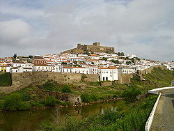 Mértola viewed from the opposite margin of the Guadiana, with the city wall and the mediaeval castle uphill