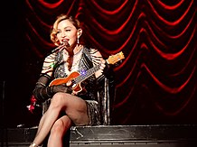 Madonna in a jeweled black dress playing a ukulele while singing to a microphone