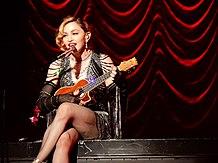 Madonna in einem juwelenbesetzten schwarzen Kleid spielt eine Ukulele, während sie zu einem Mikrofon singt