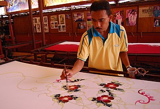 A craftsman making batik. Malaysian batik is usually patterned with floral motifs with light colouring. Malaysian Batik.jpg