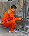 Man in orange jumpsuit working on fence at Summer Palace, Beijing.jpg